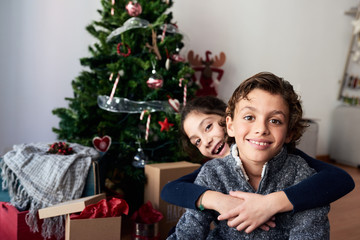 Happy children sitting against Christmas tree.