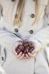 Beautiful girl holding chestnut