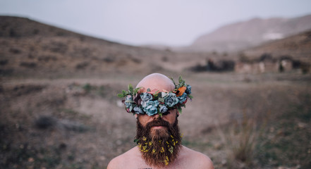 man in te desert hiding his eyes with a flowers crown