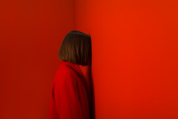 young woman leaning against a red wall