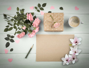 Magnolia, pink roses with blank sheet paper for greeting text and gift box, coffee cup on background of shabby wooden planks