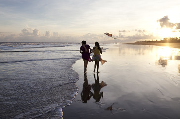 Mother and daughter enjoying running and flying kite in a beach