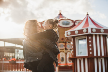 Mother holding her daughter on her arms in the amusement park
