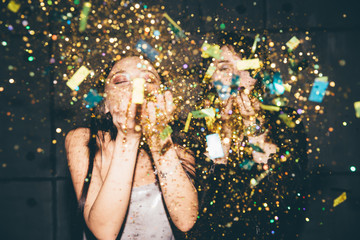 Two girl blowing golden confetti at camera