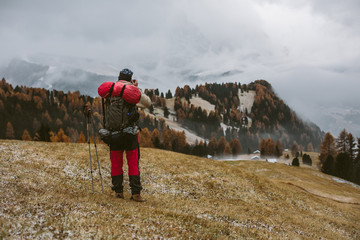 male hiker taking picture of autumnal foggy mountain landscape