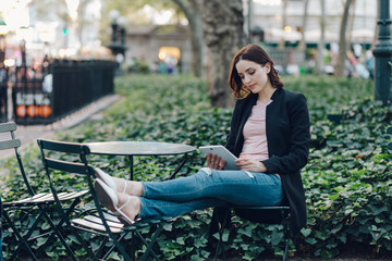 Woman relaxing at the park while using a digital tablet