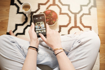 A young woman wearing distressed jeans sitting on wood floor on a rug carpet at home and holding a cell phone in hands. Around a cup of coffee and a bowl with strawberries