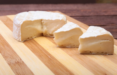 Cheese with white mold. Camembert or brie type on wood table. Healthy breakfast.