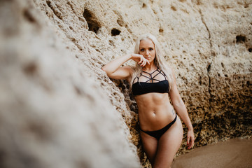Bikini beauty woman by sea and rocks at beach