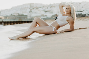 Sexy woman in wet t-shirt lying on sand at beach over sea. Summer time