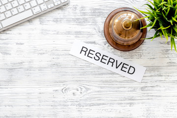 Book hotel. Word reserved near hotel service bell on light wooden table background top view copyspace