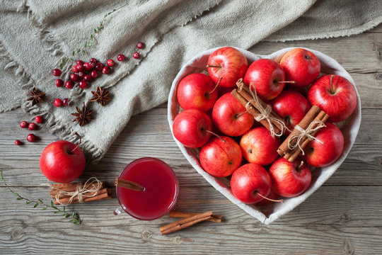 Red apples in a basket, cranberries, cinnamon and drink on a wooden background.