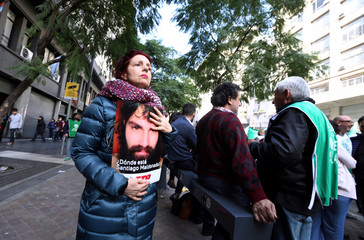 A woman holds a sign with a portrait of Santiago Maldonado during a demonstration against Argentine President Mauricio Macri's administration in Buenos Aires