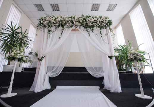 Decorated hall for a wedding ceremony with an arch