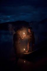 Fisherman together two old senior man help take away lantern to light.