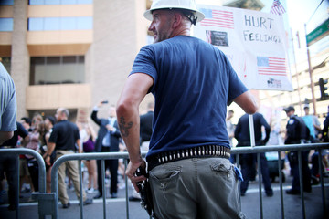 A Pro Trump supporter holds a fire arm as he faces off with protesters outside a Donald Trump campaign rally in Phoenix