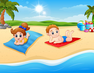 Children sunbathing on the beach mat