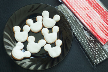Preparation for a children's party, cookies in the form of a mickey mouse and a tube for drinks