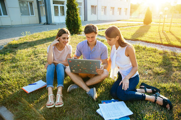 Classmate, education and teenage concept. Friendly students teenagers with laptop are studying outdoors together
