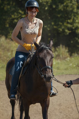 Horseback riding lessons - young woman riding a horse