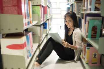 Young pretty Asian student was reading in the library. Education concept.