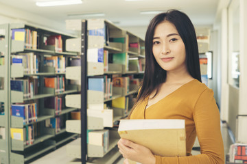Young pretty Asian student smiling to camera. Education concept.