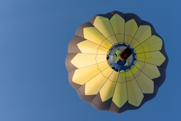 A Yellow and Black Balloon with a wicker basket carrying passengers in flight against a deep blue cloudless sky.  Image has copy space. Photographed from below.