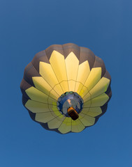 Yellow and Black Balloon in Flight with a wicker basket carrying passengers. Photographed from below. Image has copy space.
