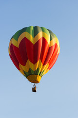 Yellow, Red and Green Balloon in Flight with cloudless sky behind. The balloon colors make a chevron design. The wicker basket carries passengers that are not recognizable.