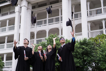 Group of Successful students with congratulations together throwing graduation hats in the air and celebrating. Education concept.
