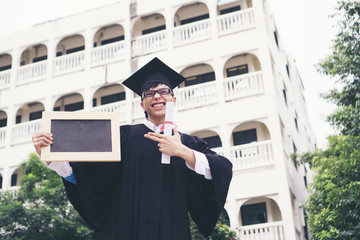 Happy graduate student holding a chalkboard in hand. Education concept.