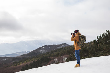 Tourist taking photo of winter mountains. Outdoor style, beige parka, backpack, jeans