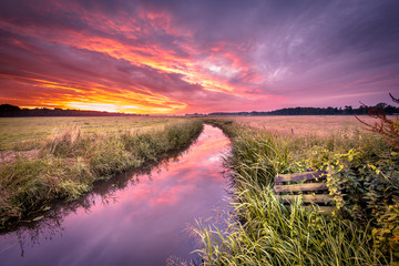 Warm indian summer sunrise over lowland river in vintage colors