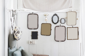 White wall with a lot of different decorative and vintage empty frames. Place for picture, text, logo, photo