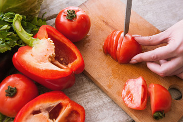 Tomatoes cutting on wooden desk by unrecognizable woman. Red pepper, and parsley nearby on table, cooking process of fresh vegetables salad