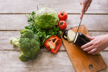 Eggplant cutting on wooden desk by unrecognizable woman. Red pepper, broccoli, tomatoes, cabbage and parsley nearby, top view picture