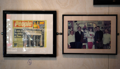A framed newspaper clipping and a photograph of Princess Diana with cafe workers are seen on the wall of the Cafe Diana in London