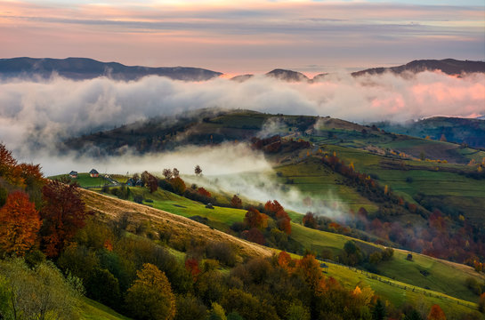 rising cloud covers rural fields in mountains