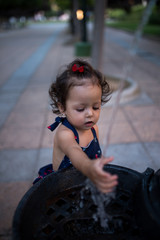niña bebé se moja la mano en la fuente de un parque