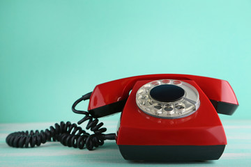 Red retro telephone on wooden table