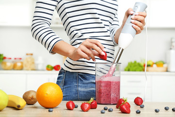 Young woman cooking smoothie in blender