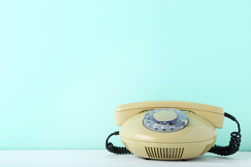 Beige retro telephone on white wooden table