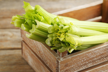 Wall Mural - Celery in crate on grey wooden table