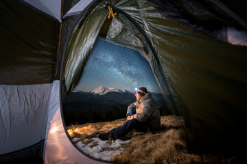 View from inside a tent on the male tourist have a rest in his camping in the mountains at night. Man with a headlamp sitting near campfire under beautiful night sky full of stars and milky way Wall mural