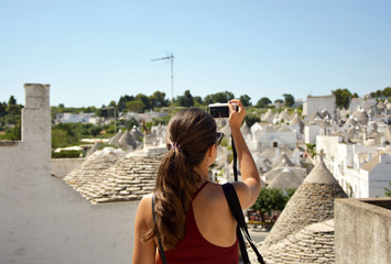 Tourist taking travel picture with mirrorless camera of Alberobello trulli cityscape during summer holidays. Unrecognizable female young adult enjoying Italy vacations in red dress.