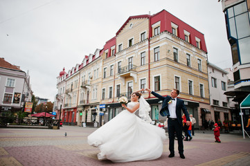Wedding couple dancing on the square in the city centre with old buildings on the background.
