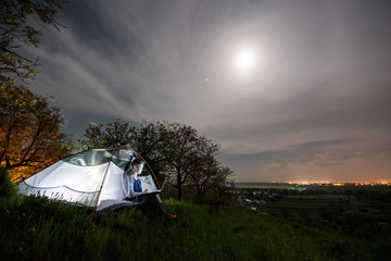 Woman using her laptop in the camping at night. Woman sitting in the tent under cloudy sky with the moon. On the background luminous village