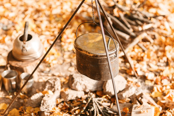 Cooking over a campfire in a cast iron pot. Cast iron pot for soup hanging over the fire campfire.