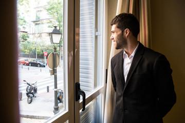 Young man wearing black elegant suit standing near window looking away.