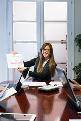 Young businesswoman showing paper with statistics to colleague